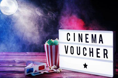 Cinema voucher concept with smoky atmosphere, shining spotlight, 3d glasses and popcorn with pretty blue and pink lighting and copy space Stok Fotoğraf
