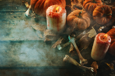 Halloween concept of candles, pumpkins and bones against smoky wooden background