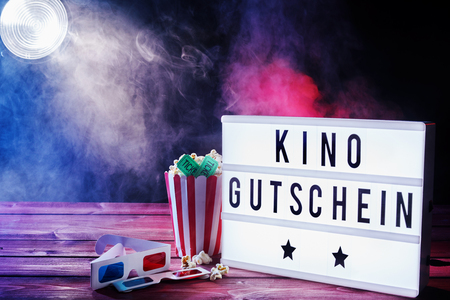 Cinema movie theme with popcorn, 3d glasses and tickets illuminated by a spotlight shining through a smoky background with kino gutschein written on a word board. Stok Fotoğraf