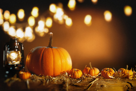 Halloween or Thanksgiving background with fresh fall pumpkins on straw lit by a burning lantern and sparkling part lights behind with copy space