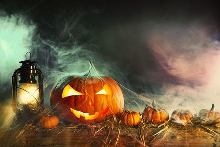 Tema di Halloween con jack-o-lantern sotto ragnatela con lampada vintage contro sfondo scuro fumoso