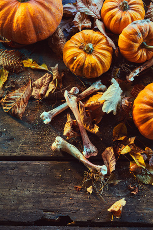 High angle view of bones among pumpkins and dry autumn leaves against wooden background