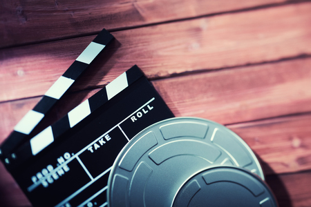 Clapboard with film tapes against wooden background Stock Photo