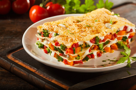Tasty portion of Italian vegetable lasagna with melted mozzarella, colorful fresh veggies and pasta serced on a plate as a healthy appetizer