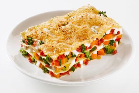 메뉴 및 광고에 대 한 흰색 배경 위에 접시에 봉사하는 다채로운 신선한 채소의 혼합으로 만든 신선한 야채 라자 냐의 건강 한 부분