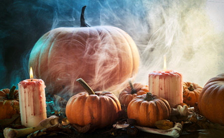 Smoky spooky Halloween background of fresh pumpkins, dried bones, leaves and burning candles in a smoky atmospheric forest outdoors with copy space