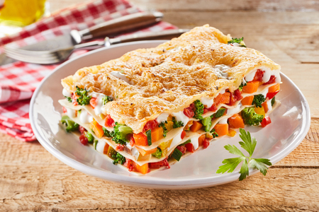 Large portion of healthy colorful vegetable lasagne made with assorted fresh veggies layered with melted mozzarella and pasta served on a white plate Stock Photo