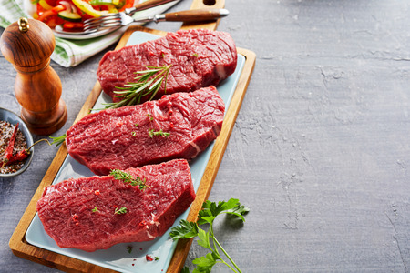 Slices of raw rump steak prepared with spices on wooden cutting board