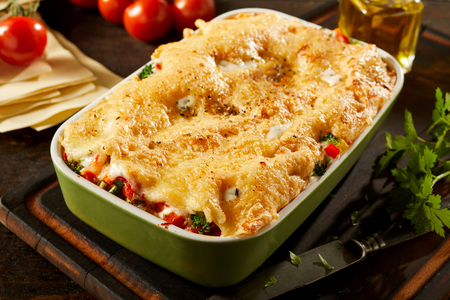 Dish of tasty cheesy vegetable lasagne with assorted fresh veggies layered with Italian pasta surrounded by fresh ingredients on a table