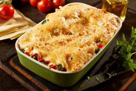 Schotel van smakelijke kaasachtige plantaardige lasagne met geassorteerde verse veggies gelaagd met Italiaanse die deegwaren door verse ingrediënten op een lijst worden omringd