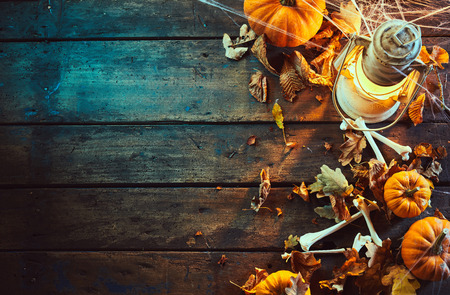 High angle view of halloween pumpkins with bones and vintage lamp under spider web against wooden background Stock Photo