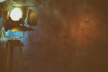 An illuminated stage light amongst dry ice smoke on a plain, dark background with copy space.
