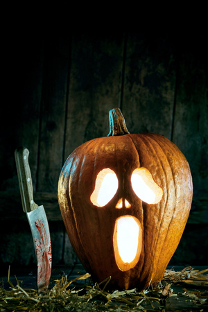 Halloween theme of spooky jack-o-lantern with bloody knife against wooden background
