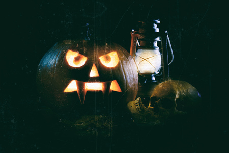Halloween concept of spooky jack-o-lantern with skull and vintage lamp