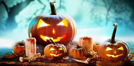 Spooky Halloween banner in a misty forest with an arrangement of glowing evil jack-o-lantern pumpkins and burning candles with dried leaves, bones and copy space