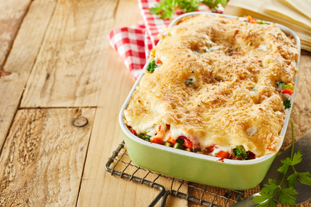 Casserole dish of fresh Italian vegetable lasagna topped with grated cheese standing cooling on a wire rack on a rustic table with copy space Stock Photo