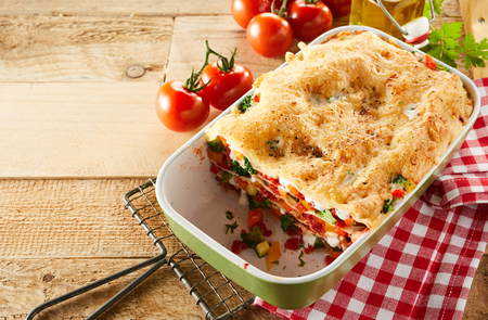 Healthy tasty dish of fresh vegetable lasagna with melted cheese and Italian pasta served on rustic wooden with a napkin and ingredients, copy space alongside