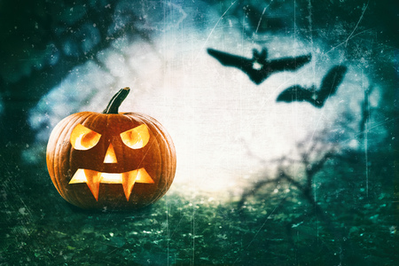 Halloween theme of spooky jack o lantern against flying bats