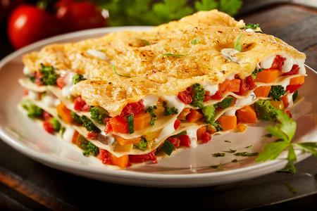 色とりどりの新鮮な野菜のラザニアを間近に見るパスタのシーツの間に重なった溶かしたモッツァレラのブロッコリー、ピーマン、トマトのプレー 写真素材