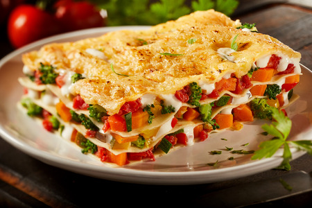 Close up view of colorful fresh vegetable lasagna served on a plate with broccoli, sweet peppers and tomato in melted mozzarella layered between sheets of pasta