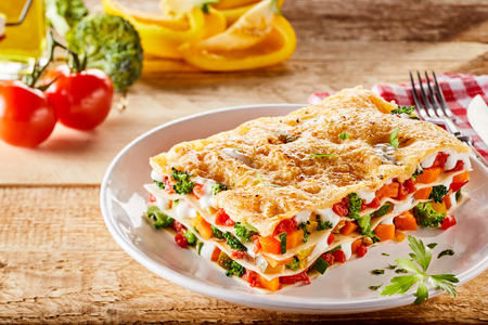 Single portion serving of a colorful appetizer of Italian vegetable lasagna made with assorted fresh veggies, melted mozzarella and pasta sheets on a rustic table