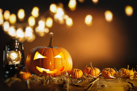 Halloween still life background with copy space and a glowing hurricane lamp and Jack-o-lantern pumpkin on straw with a bokeh of party lights above