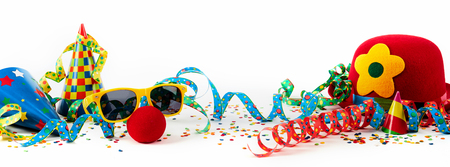 Party or carnival banner with fancy dress accessories and colorful decorations with hats, streamers and confetti in a colorful still life on white