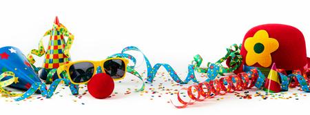 Fête ou bannière de carnaval avec accessoires de déguisements et décorations colorées avec des chapeaux, des banderoles et des confettis dans une nature morte colorée sur blanc