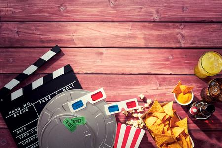 Varios accesorios para películas y películas, incluyendo una claqueta junto con palomitas de maíz, gafas 3D, entradas y refrescos en una imagen temática de la cinematografía con espacio de copia de grano de madera de madera. Foto de archivo - 88255912