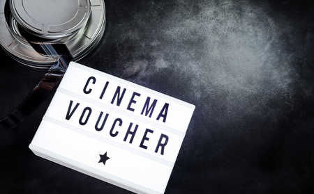 Cinema voucher written on a word board beside a movie film roll canister with a dark background and copy space. 版權商用圖片