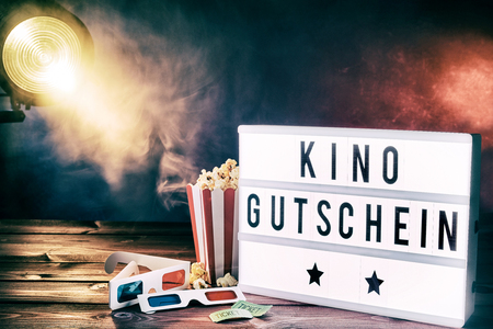 Cinema movie theme with popcorn, 3d glasses and tickets illuminated by a spotlight shining through a smoky background with kino gutschein written on a word board. Фото со стока