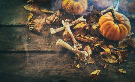 Halloween theme of bones, pumpkins among dry autumn leaves against wooden background