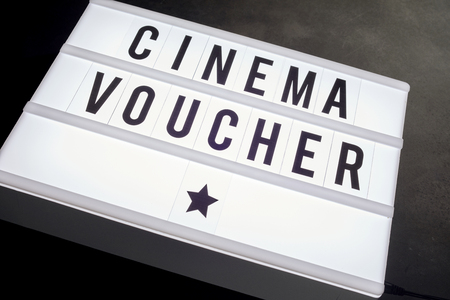 A close up of cinema voucher written on word board with stars in a movie themed image with a dark background.