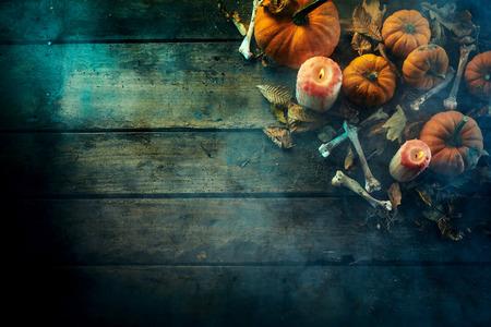 Halloween theme of pumpkins, bones and candles against dark wooden background Reklamní fotografie