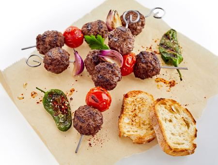 Grilled or fried meatballs with sliced baguette toast and roasted peppers and tomatoes on oven paper isolated on white viewed from above