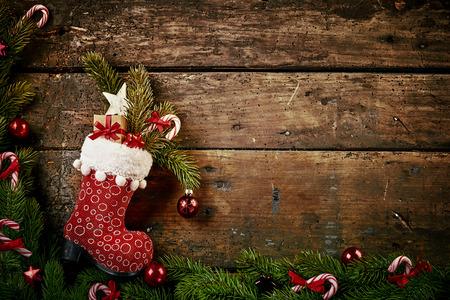 カラフルなパターン赤ブートまたはストッキングの装飾と松やキャンディー杖の境界線と素朴な木の背景にギフトでいっぱいお祝いクリスマス国境 写真素材