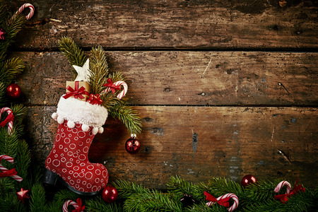 Festive Christmas border with colorful patterned red boot or stocking filled with decorations, and a gift on rustic wood background with pine and candy cane border