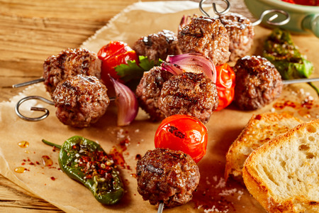 Traditional ground spicy meatball kebabs with onion and tomato served with toasted baguette and roasted peppers on rustic paper Stock Photo