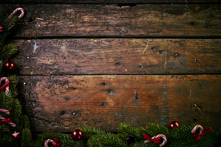 Festive rustic Christmas border on old vintage wood with copy space formed of fresh pine and candy canes