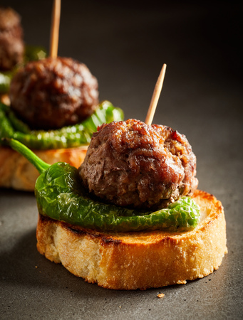 Roasted meatballs with green pepper served on slice of baked bread Stockfoto