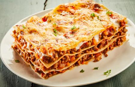 Gedeelte heerlijke kaasachtige lasagne van rundvlees geserveerd op een bord met de lagen noedels, vlees en mozzarella, geschikt om in een menu te adverteren