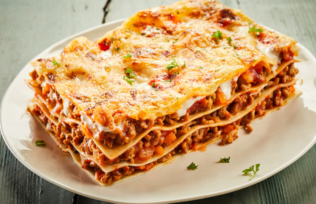 Portion of delicious cheesy beef lasagne served on a plate showing the layers of noodles, meat and mozzarella cheese suitable for advertising in a menu Foto de archivo