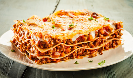 Slice of delicious beef lasagne on a plate garnished with chopped fresh parsley and viewed close up on the side showing the layers