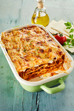 Tasty lasagne covered with cheese in baking dish on wooden table Stock Photo