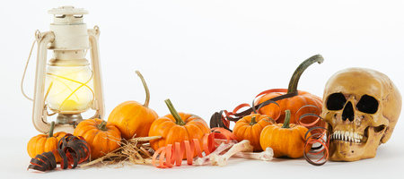 Grisly macabre Halloween panorama banner with a still life of pumpkins, skull, dried bones, vintage lanterns and streamers with copy space Stock Photo