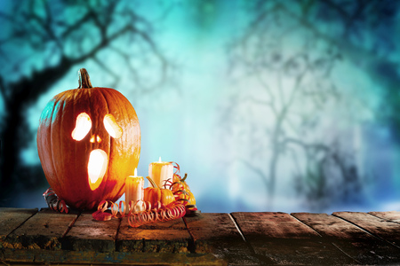 Spooky halloween theme of jack o lantern with candles standing on wooden table against trees