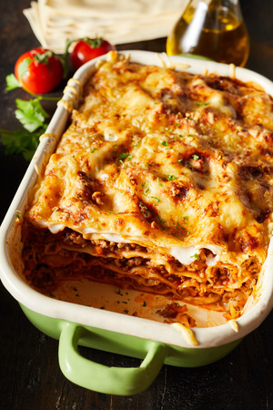 Tasty dish of oven-baked lasagne topped with golden melted mozzarella cheese viewed close up from above with fresh ingredients