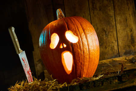 Gruesome Halloween Jack-o-lantern background with a bloodied knife alongside a glowing pumpkin with ghostly face Stock Photo
