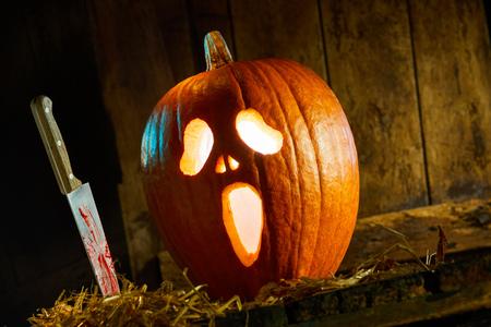 Raccapricciante Halloween Jack-o-lantern sfondo con un coltello insanguinato accanto a una zucca incandescente con faccia spettrale Archivio Fotografico - 88622826