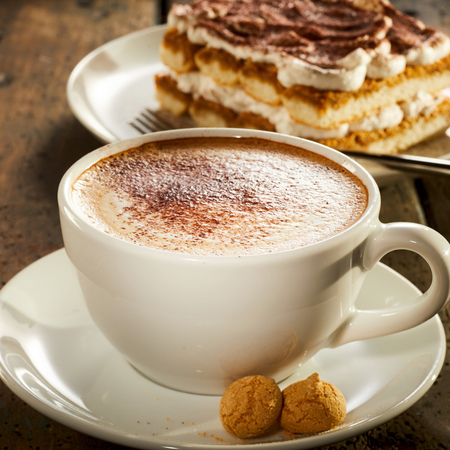 Freshly made cup and saucer of frothy cappuccino coffee served with two small macaroons and cake in square format
